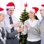 Cheerful employees in festive Christmas hats making a toast